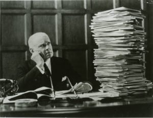 man_looking_at_stack_of_papers